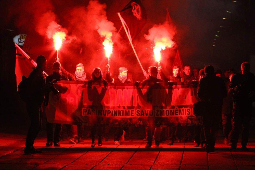 "Nazis with state and ""Celtic Cross"" flags march in a torchlight procession, protesting against refugees in Lithuania. October 17, 2015. Photo: Delfi.lv"