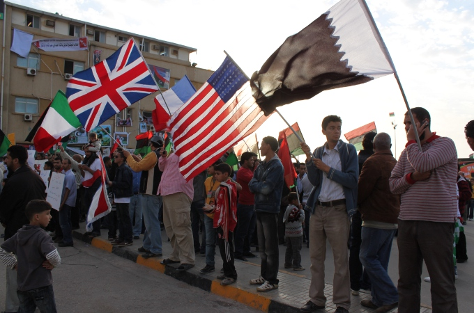 Benghazi residents hold Italian, British, French, American, Qatari flags, 2011.