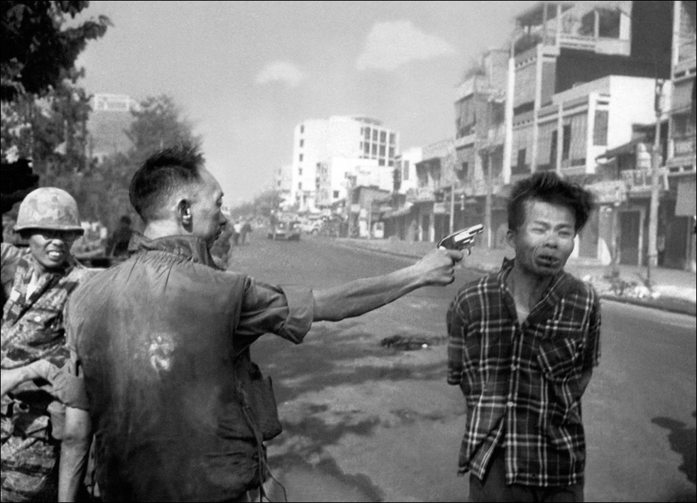 "Nguyen Ngoc Loan, chief of the National Police, and an American collaborator, fires his pistol into the head of suspected Viet Cong officer Nguyen Van Lem on a Saigon street on February 1, 1968, early in the Tet Offensive. In 1975, during the fall of Saigon, Loan fled South Vietnam. He moved to the United States, and opened a pizza restaurant in the Washington, D.C. suburb of Burke, Virginia at Rolling Valley Mall called ""Les Trois Continents.""[11] In 1991, he was forced into retirement when he was recognized and his identity publicly disclosed. Photographer Eddie Adams recalled that on his last visit to the pizza parlor, he had seen written on a toilet wall, ""We know who you are, fucker""."