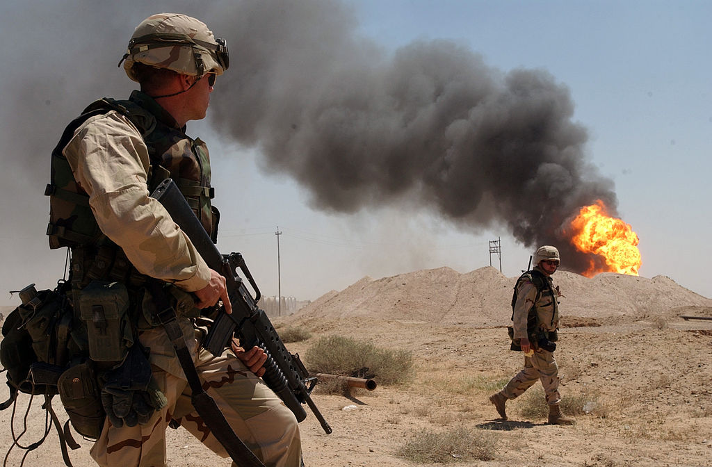 A U.S. soldier stands guard duty near a burning oil well in the Rumaila oil field, 2 April 2003