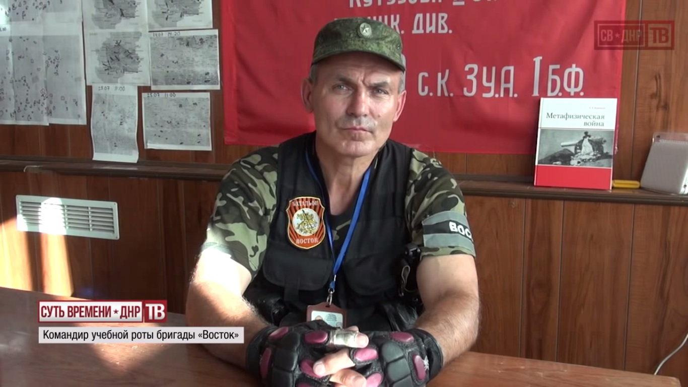 """Vostok"" battalion training company commander ""Chika"" with the Banner of Victory in the Great Patriotic War and Sergei Kurginyan's textbook ""Metaphysical Warfare"" behind him. Still from EoT DPR TV Episode 144"