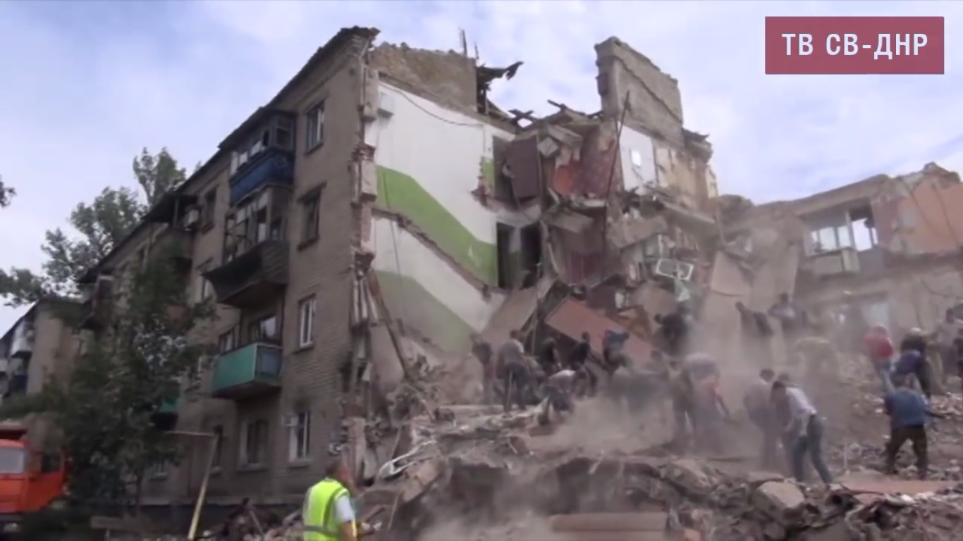 Aftermath Ukrainian airstrike on Snezhnoye town near Donetsk. Three buildings were destroyed: a private house, a 5-storey residential building and an administrative building. Over 10 people were killed, over 50 were injured by the airstrike. July 15, 2014. Still from EoT TV DPR Issue 24.