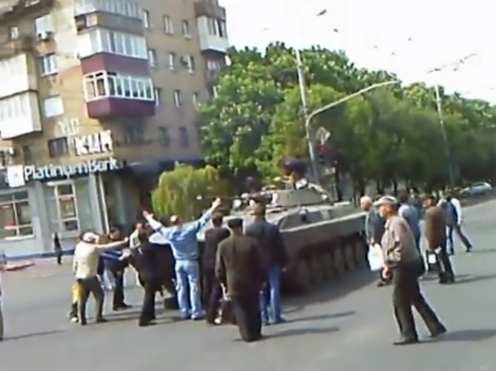 Residents of Mariupol try to stop one of the IFVs near Platinum Bank. Seconds later it rushes away. May 9, 2014.