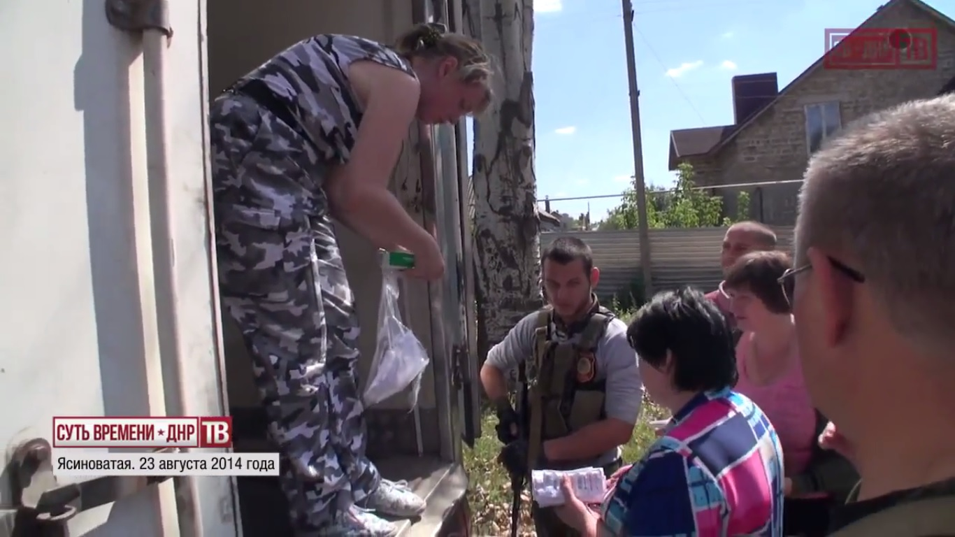 Vostok battalion medical service worker handing out medicine to residents of Yasinovataya. August 23, 2014.  Still from EoT-DPR TV Issue 140