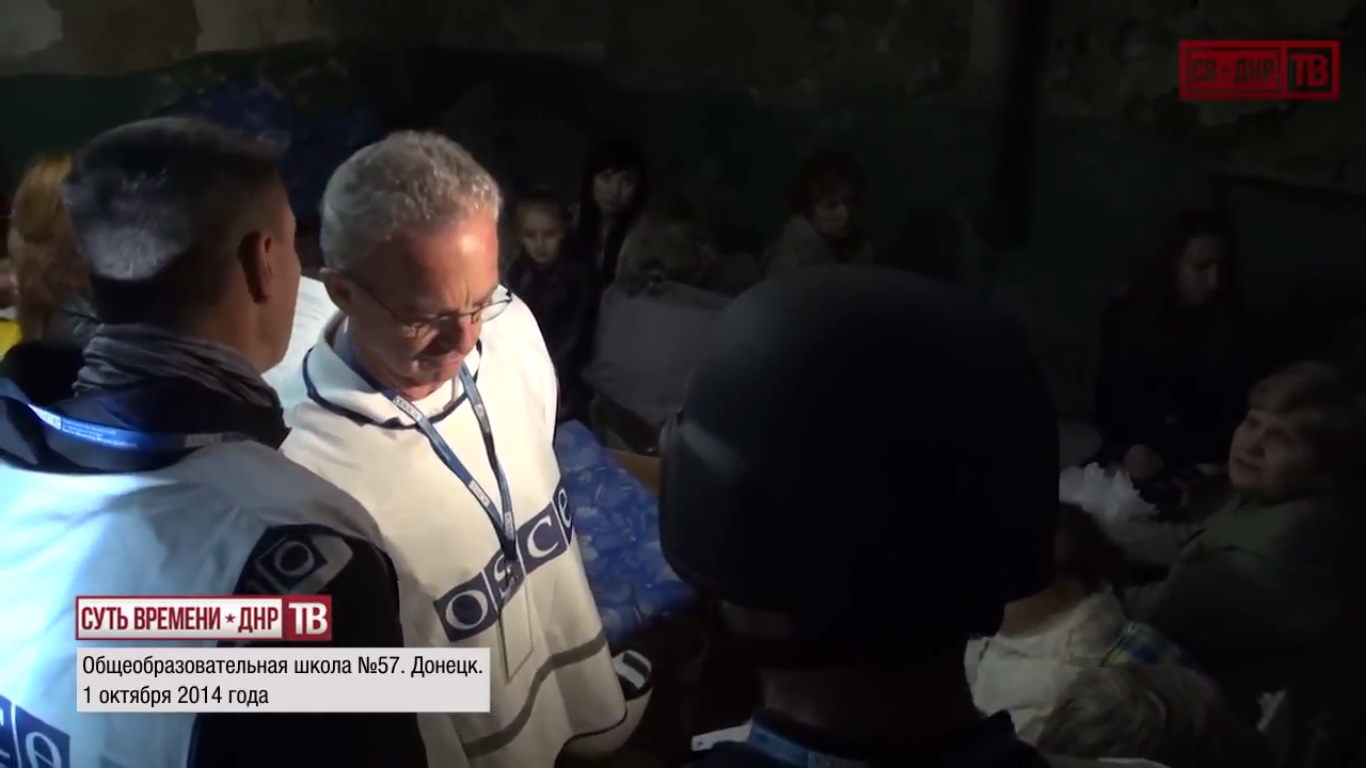 """The OSCE monitor listening to the translation of what the woman says: """"Why everyone cares if one person dies in another country, but nobody's listening when hundreds, thousands get killed here. After all, the whole world needs to stand up and see what is happening here. Because today they came for us, tomorrow they will come for them. Don't you understand that a horrible enemy is rising? It must be destroyed know."""" October 1, 2014.  Still from EoT-DPR TV Issue 213"""