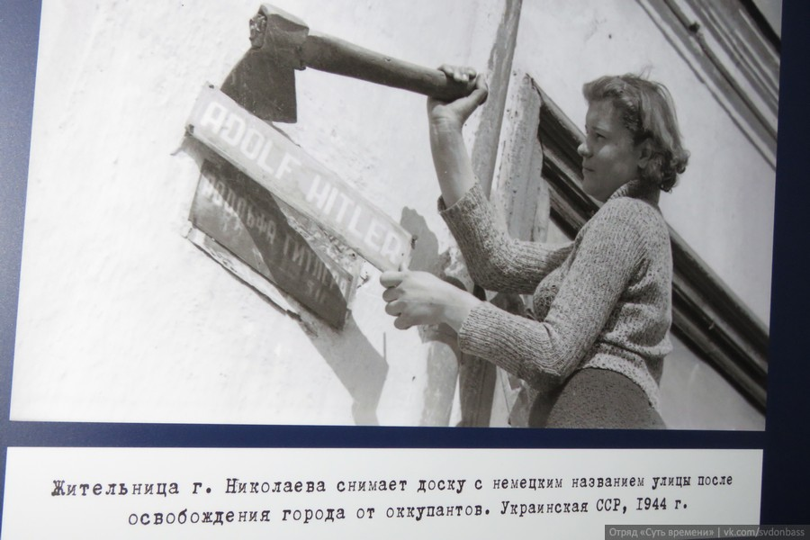 Resident of Nikolaev city takes of the street sign after the city was liberated by the Red Army. Ukrainian Soviet Socialist Republic, 1944.