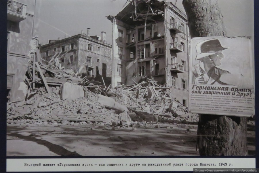 "Caption on the poster: ""German army is your defender and friend!"" on the destroyed street of Bryansk, 1943"